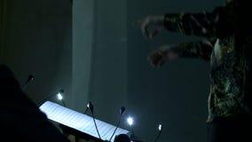 As mãos moventes de um condutor de orquestra que dirige os músicos Tiro do close up filme