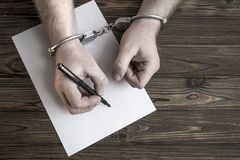 As mãos nas algemas escrevem uma participação no fundo de uma tabela de madeira imagens de stock royalty free