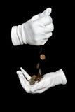 As mãos nas luvas brancas derramam moedas finas Imagens de Stock