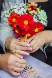 As mãos no close-up dispararam dos anéis das alianças de casamento das flores em pessoas adultas de aniversário de casamento Foto de Stock Royalty Free