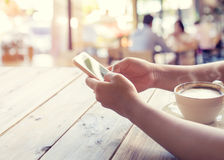 As mãos novas bonitas do ` s da mulher do moderno que guardam o telefone esperto móvel com o copo de café quente no café compram, Imagens de Stock Royalty Free