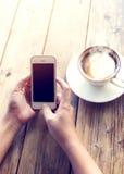 as mãos novas bonitas do ` s da mulher do moderno que guardam o telefone esperto móvel com o copo de café quente no café compram Imagens de Stock