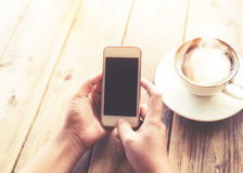 as mãos novas bonitas do ` s da mulher do moderno que guardam o telefone esperto móvel com o copo de café quente no café compram Imagens de Stock Royalty Free