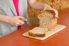As mãos pequenas cortam o pão Imagens de Stock