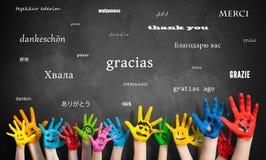 As mãos pintadas das crianças na frente de um quadro-negro com a mensagem 'agradecem-lhe 'em muitas línguas imagens de stock royalty free