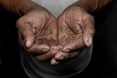 As mãos pobres do ` s do ancião imploram-no pela ajuda O conceito da fome ou da pobreza Foco seletivo foto de stock