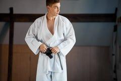 As mãos que apertam o cinturão negro no homem vestiram-se no quimono imagem de stock