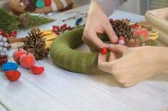 As mãos que criam a grinalda e a fita do Natal curvam-se em uma placa de madeira Fotos de Stock Royalty Free