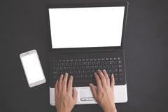 As mãos que datilografam no portátil com telefone celular no lado, zombam acima fotografia de stock royalty free