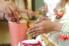 As mãos que derramam a bênção molham nas mãos da noiva do casamento tailandês Imagens de Stock Royalty Free