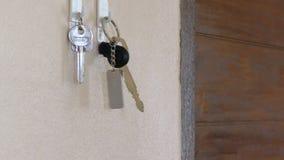 As mãos que estão indo pôr chaves de uma casa penduraram em um gancho na parede filme