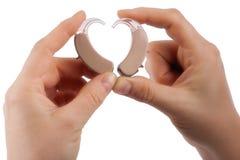 As mãos que formam um coração dão forma das próteses auditivas isoladas fotos de stock royalty free
