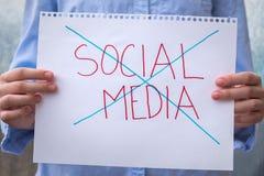 As mãos que guardam o sinal com meios sociais das palavras cruzaram-se para fora fotografia de stock royalty free