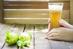 As mãos que guardam o suco do noni e o noni de vidro frutificam na tabela de madeira Foto de Stock