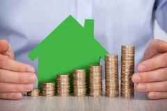 As mãos que protegem euro- moedas empilhadas e a casa modelam Fotografia de Stock