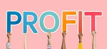 As mãos que sustentam as letras coloridas que formam a palavra lucram fotos de stock royalty free