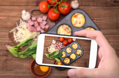 As mãos que tomam a foto egg queques com presunto, queijo e vegetais com smartphone imagens de stock