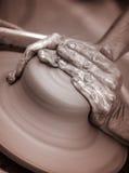 As mãos que trabalham na cerâmica rodam, artístico tonificado Fotografia de Stock