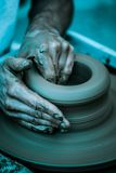 As mãos que trabalham na cerâmica rodam, artístico tonificado Foto de Stock
