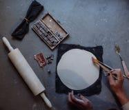 As mãos que trabalham na cerâmica rodam, estilo retro tonificado Imagem de Stock