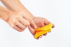 As mãos rasgam a etiqueta o do bloco no fundo branco Imagens de Stock
