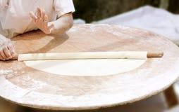 As mãos rolam a massa de pão Fotografia de Stock
