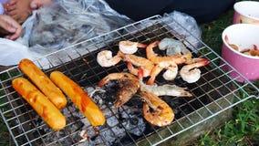 As mãos são grade ou assado grelhado do marisco com carvão vegetal no partido video estoque