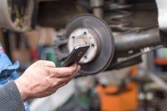 As mãos sujas do trabalhador estão usando um telefone esperto foto de stock