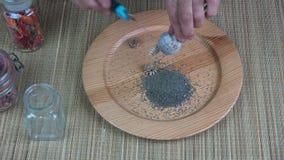 As mãos superiores do jardineiro da mulher cortaram a cabeça da papoila e sementes da coleta vídeos de arquivo