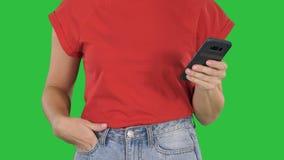 As mãos terra arrendada da mulher bonita, usando o telefone esperto em uma tela verde, chave do croma filme