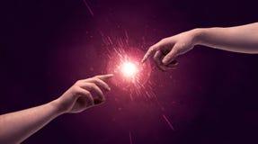 As mãos tocantes iluminam acima a faísca no espaço Imagens de Stock
