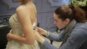 As mãos traseiras da vista atam acima o espartilho branco da seda do vestido de casamento filme