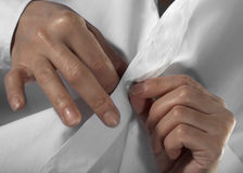 As mãos unbutton uma tecla Fotografia de Stock