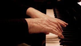 As m?os da mulher superior que jogam o piano Vista lateral ascendente pr?xima das m?os idosas e dos dedos que jogam uma m?sica video estoque
