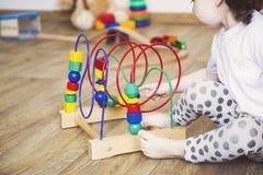 As m?os de uma menina da crian?a que joga brinquedos Desenvolvimento de habilidades de motor finas foto de stock