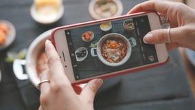 As m?os f?meas tomam fotos do alimento pelo smartphone moderno closeup 4K video estoque