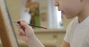 As m?os novas do artista, artista pequeno da mulher pintam uma lona com escova, sentando uma tabela e uma tra??o na lona processo filme