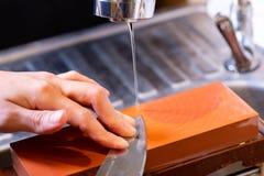 as m?os profissionais do cozinheiro chefe da mulher guardam a faca para afiar na m? pedra profissional superior de jap?o faca que fotografia de stock