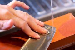 as m?os profissionais do cozinheiro chefe da mulher guardam a faca para afiar na m? pedra profissional superior de jap?o faca que imagens de stock
