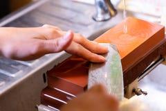 as m?os profissionais do cozinheiro chefe da mulher guardam a faca para afiar na m? pedra profissional superior de jap?o faca que imagens de stock royalty free