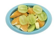 As maçãs alaranjadas do quivi das uvas sem sementes cortaram nas partes em sh oval azul Foto de Stock Royalty Free