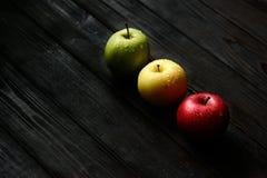 As maçãs amarelas verdes vermelhas em uma fileira diagonal com água deixam cair na tabela de madeira preta, luz traseira Fotografia de Stock Royalty Free
