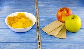 As maçãs das microplaquetas panam a fita do centímetro em um centímetro de madeira azul do fundo foto de stock royalty free