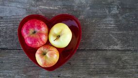 As maçãs doces frescas no coração vermelho deram forma ao vaso fotografia de stock royalty free
