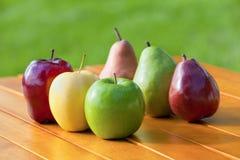As maçãs e as peras alinharam junto em uma tabela imagens de stock