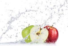As maçãs frescas com água espirram sobre o fundo branco imagem de stock