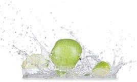 As maçãs frescas com água espirram sobre o fundo branco foto de stock