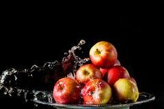 As maçãs que encontram-se no lado de prata e na água de voo Foto de Stock