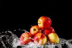 As maçãs que encontram-se no lado de prata e na água de voo Imagens de Stock Royalty Free