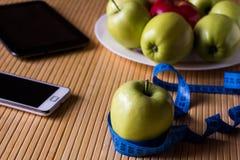 As maçãs são no AON uma placa na tabela de bambu clara Está próximo a tabela Foto de Stock